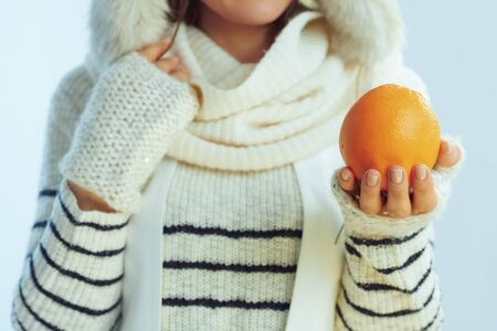 Closeup on happy young 40 years old woman in white striped sweater, scarf and ear flaps hat showing an orange on winter light blue background.