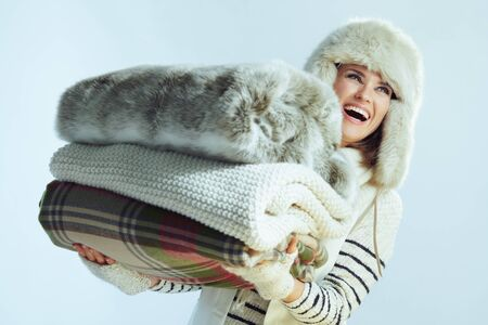 smiling young woman in white striped sweater, scarf and ear flaps hat holding a stack of warm blankets isolated on winter light blue background. 免版税图像