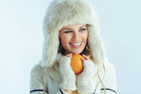 happy young female in white striped sweater, scarf and ear flaps hat with an orange looking aside on winter light blue background.