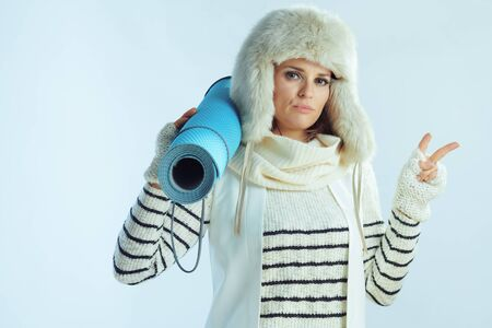 cool modern 40 years old woman in white striped sweater, scarf and ear flaps hat with fitness mat showing victory gesture against winter light blue background.