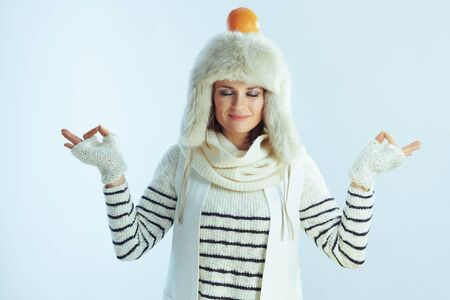 relaxed elegant female in white striped sweater, scarf and ear flaps hat with orange on head meditating against winter light blue background. 写真素材