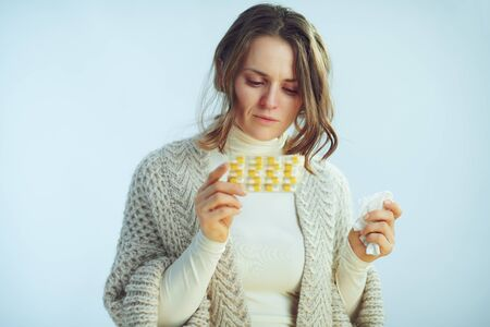 ill modern female in roll neck sweater and cardigan with napkin reading instruction on blister pack of pills isolated on winter light blue background. Stock Photo