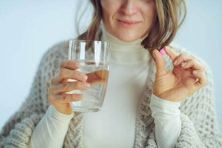 Closeup on ill modern 40 years old housewife in roll neck sweater and cardigan with cup of water showing pill on winter light blue background.
