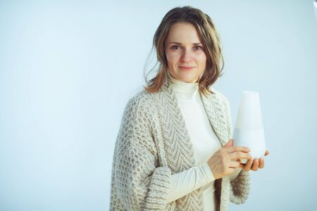 sick elegant middle age housewife in roll neck sweater and cardigan holding aroma lamp on winter light blue background. Stock Photo