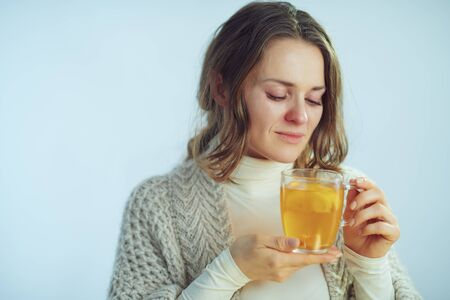 sick elegant 40 years old housewife in roll neck sweater and cardigan drinking cup of hot tea with ginger, lemon and honey against winter light blue background.