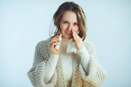 Portrait of ill modern middle age woman in roll neck sweater and cardigan with napkin using nasal spray isolated on winter light blue background. Stock Photo