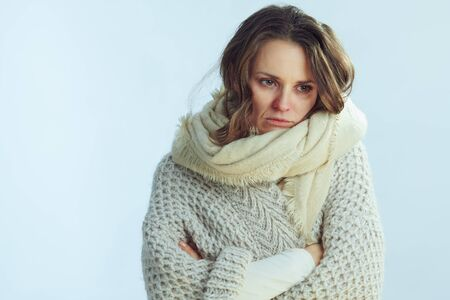 Portrait of unhappy ill elegant housewife in roll neck sweater and cardigan on winter light blue background. Stock Photo