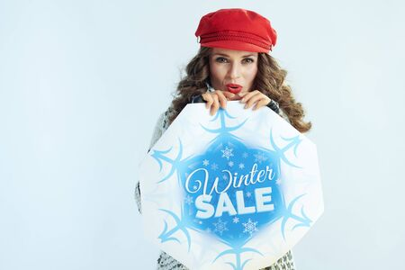 stylish middle age woman with long brunette hair in sweater, scarf and red hat with winter sale banner warming hands with warm breathe against winter light blue background.