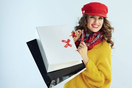 Portrait of smiling stylish woman with long brunette hair in sweater, scarf and red hat showing shopping bags on winter light blue background.