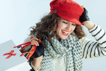 smiling stylish woman with long brunette hair in sweater, scarf and red hat with shopping bags against winter light blue background.