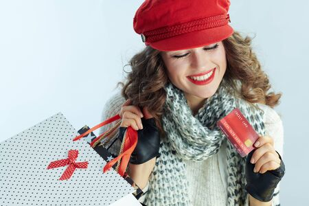 smiling stylish middle age woman with long brunette hair in sweater, scarf and red hat with shopping bags and credit card against winter light blue background. Stockfoto