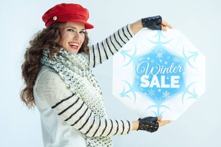 Portrait of smiling young woman with long brunette hair in sweater, scarf and red hat showing winter sale banner against winter light blue background. Banque d'images