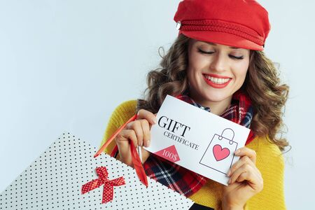 smiling stylish female with long brunette hair in sweater, scarf and red hat with shopping bags looking at gift certificate against winter light blue background.