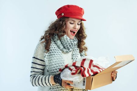 surprised trendy female with long brunette hair in sweater, scarf and red hat looking inside opened parcel with sweater against winter light blue background. Stockfoto