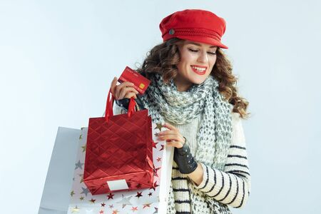 happy modern 40 years old woman with long brunette hair in sweater, scarf and red hat with shopping bags and credit card against winter light blue background.