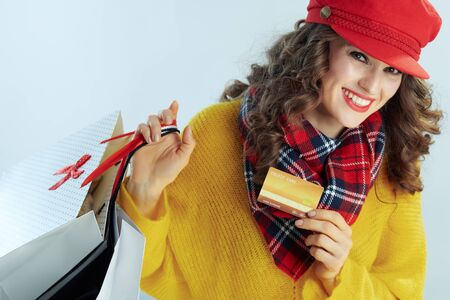 Portrait of happy stylish middle age woman with long brunette hair in sweater, scarf and red hat with shopping bags showing golden credit card isolated on winter light blue background. Stockfoto