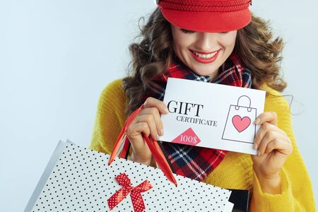 smiling modern woman with long brunette hair in sweater, scarf and red hat with shopping bags showing gift certificate isolated on winter light blue background. Banque d'images