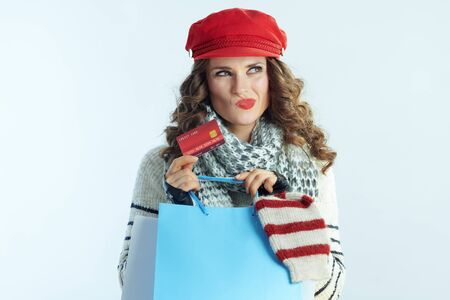 Portrait of pensive elegant woman with long brunette hair in sweater, scarf and red hat with shopping bags with sweaters and credit card against winter light blue background.