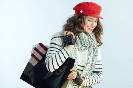 smiling stylish 40 years old woman with long brunette hair in sweater, scarf and red hat with black shopping bag with bought sweater on winter light blue background.