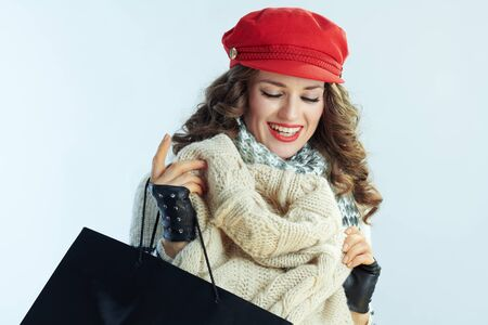 smiling elegant 40 years old woman with long brunette hair in sweater, scarf and red hat with shopping bags checking purchases isolated on winter light blue background.