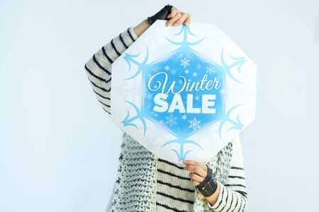 modern woman with long brunette hair in sweater, scarf and red hat showing winter sale banner against winter light blue background.
