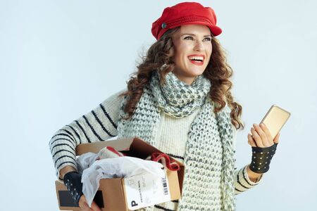 happy young 40 years old woman with long brunette hair in sweater, scarf and red hat with opened parcel and smartphone looking into the distance isolated on winter light blue background.