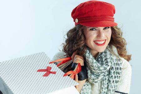 Portrait of smiling modern 40 years old woman with long brunette hair in sweater, scarf and red hat with shopping bags on winter light blue background. Stockfoto