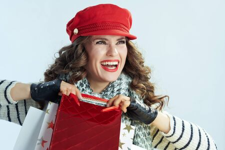 smiling young woman with long brunette hair in sweater, scarf and red hat with shopping bags looking at copy space on winter light blue background.