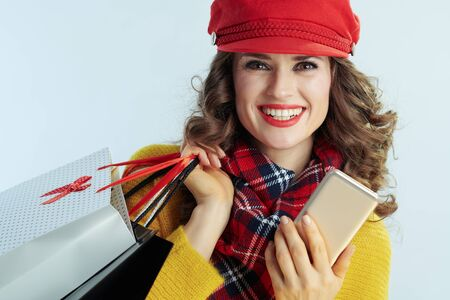 Portrait of smiling modern woman with long brunette hair in sweater, scarf and red hat with shopping bags and smartphone on winter light blue background. Banque d'images