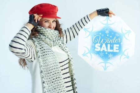 young woman with long brunette hair in sweater, scarf and red hat showing winter sale banner isolated on winter light blue background.