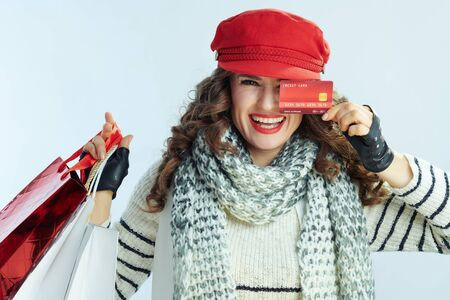 Portrait of smiling trendy middle age woman with long brunette hair in sweater, scarf and red hat with shopping bags and credit card isolated on winter light blue background.