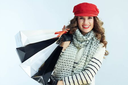 Portrait of happy stylish woman with long brunette hair in sweater, scarf and red hat with shopping bags isolated on winter light blue background. Stockfoto