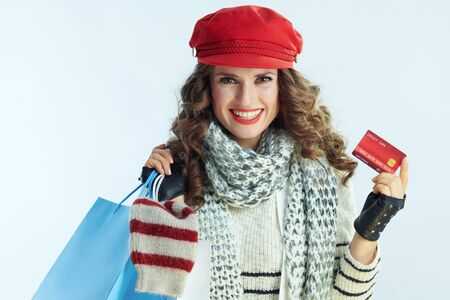 Portrait of happy middle age woman with long brunette hair in sweater, scarf and red hat with shopping bags with sweaters showing credit card isolated on winter light blue background. Stockfoto