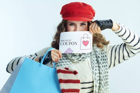 trendy woman with long brunette hair in sweater, scarf and red hat with shopping bags with sweaters showing discount coupon on winter light blue background.