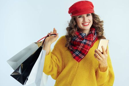 happy trendy woman with long brunette hair in sweater, scarf and red hat with shopping bags with smartphone driving the growth of social media isolated on winter light blue background.
