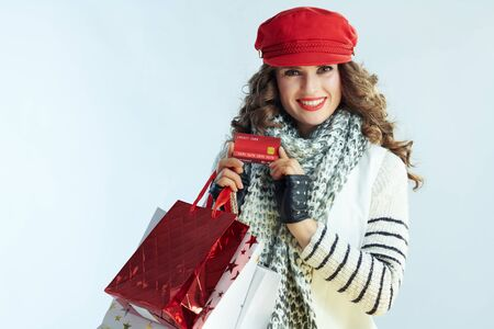 Portrait of happy young 40 years old woman with long brunette hair in sweater, scarf and red hat with shopping bags showing credit card isolated on winter light blue background. Stockfoto