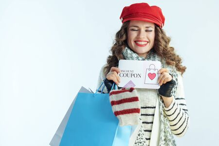 smiling young 40 years old woman with long brunette hair in sweater, scarf and red hat with shopping bags with sweaters showing discount coupon on winter light blue background.