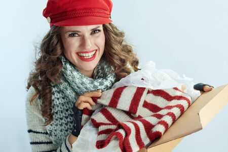 Portrait of happy stylish middle age woman with long brunette hair in sweater, scarf and red hat holding opened parcel and checking delivered sweater isolated on winter light blue background. Stockfoto