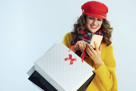 happy young 40 years old woman with long brunette hair in sweater, scarf and red hat with shopping bags making online shopping on e-commerce website against winter light blue background.