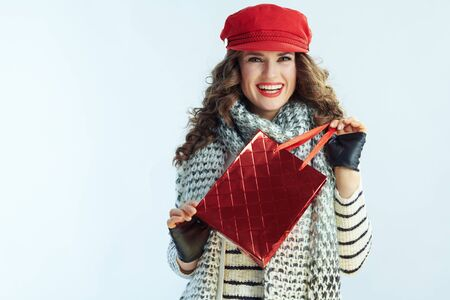 Portrait of smiling modern 40 years old woman with long brunette hair in sweater, scarf and red hat with red shopping bag against winter light blue background.