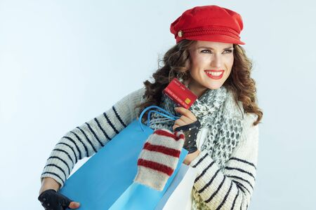 happy young woman with long brunette hair in sweater, scarf and red hat with shopping bags with sweaters and credit card looking at copy space against winter light blue background.