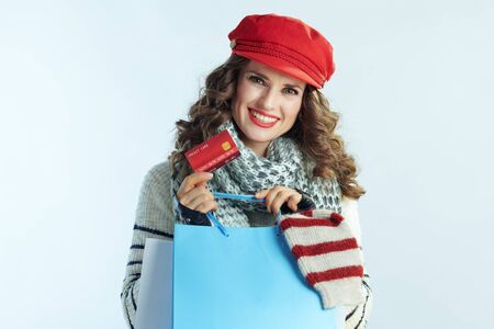 Portrait of happy modern woman with long brunette hair in sweater, scarf and red hat with shopping bags with sweaters showing credit card against winter light blue background.
