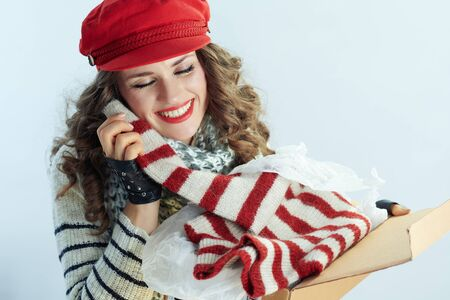happy trendy middle age woman with long brunette hair in sweater, scarf and red hat holding opened parcel and enjoying delivered sweater isolated on winter light blue background. Stock Photo