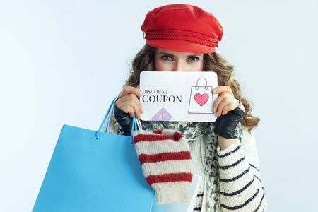 modern woman with long brunette hair in sweater, scarf and red hat with shopping bags with sweaters showing discount coupon on winter light blue background.