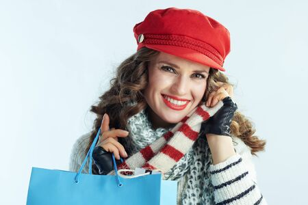 Portrait of happy trendy female with long brunette hair in sweater, scarf and red hat with shopping bags enjoying purchased sweater on winter light blue background.