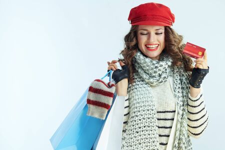 smiling trendy woman with long brunette hair in sweater, scarf and red hat with shopping bags with sweaters showing credit card against winter light blue background.