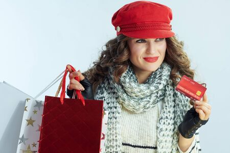 pensive young woman with long brunette hair in sweater, scarf and red hat with shopping bags and credit card isolated on winter light blue background. Stockfoto