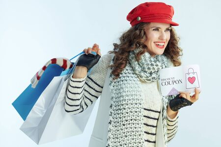 happy modern female with long brunette hair in sweater, scarf and red hat with shopping bags with sweaters and discount coupon looking at copy space on winter light blue background. Stockfoto