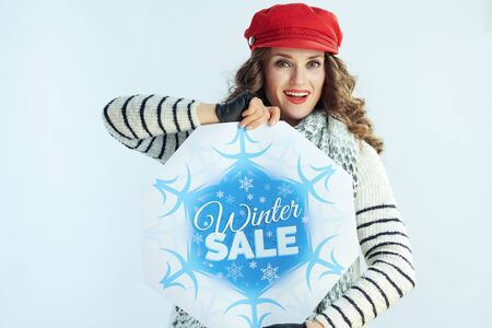 surprised stylish woman with long brunette hair in sweater, scarf and red hat showing winter sale banner on winter light blue background.