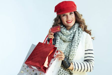 Portrait of happy elegant 40 years old woman with long brunette hair in sweater, scarf and red hat with shopping bags and credit card isolated on winter light blue background.